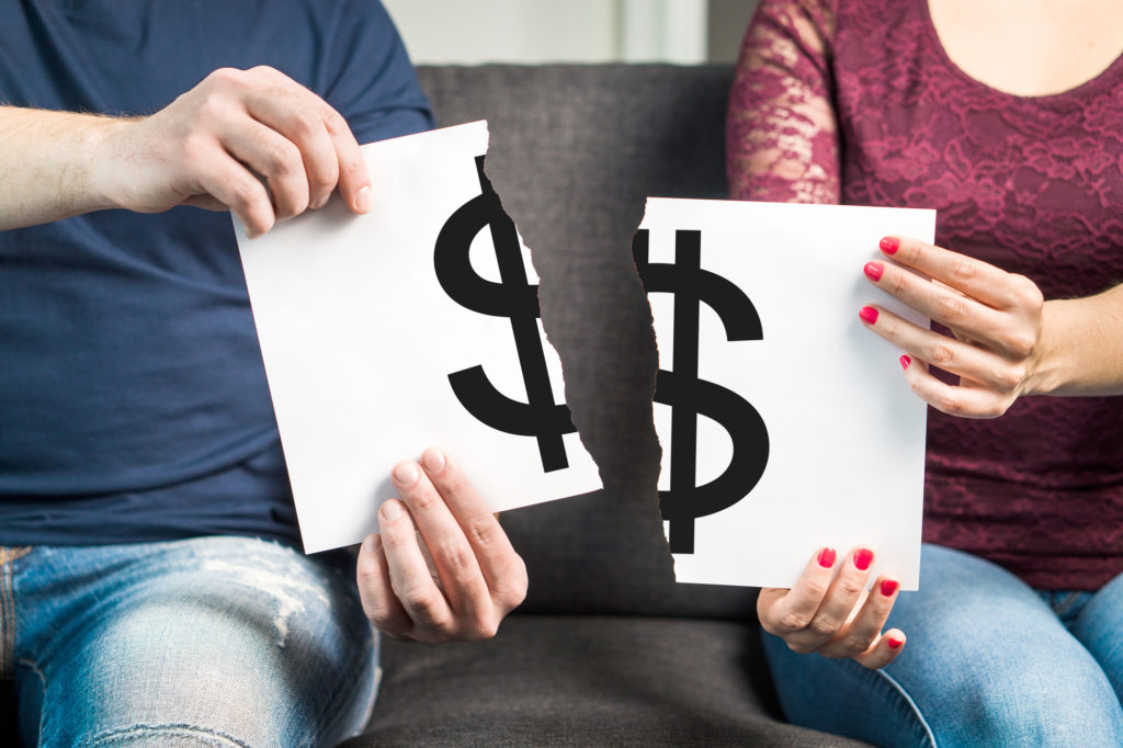 Man and woman holding ripped paper with dollar sign.